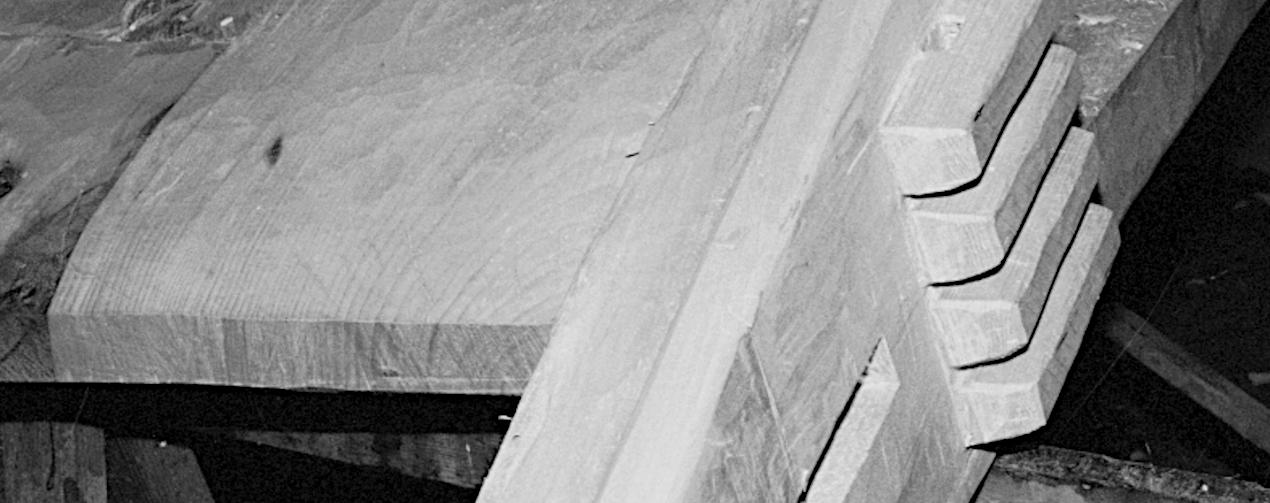 Udsnit af stævnklodsen, set fra oven, med fire klamper og hul til stævntræet i rælingshornet.